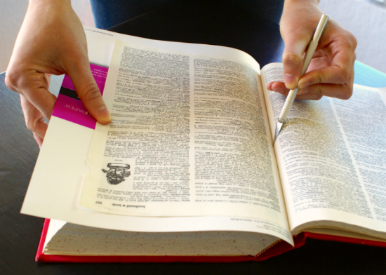 Cutting a book page out of a damaged dictionary.