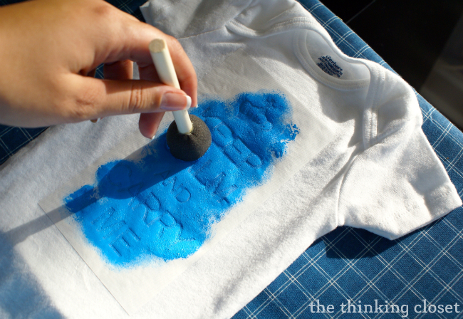Applying the fabric paint to the onesie!