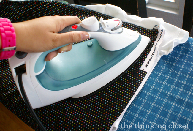 Heat setting the fabric paint by pressing it with a hot dry iron on both sides.