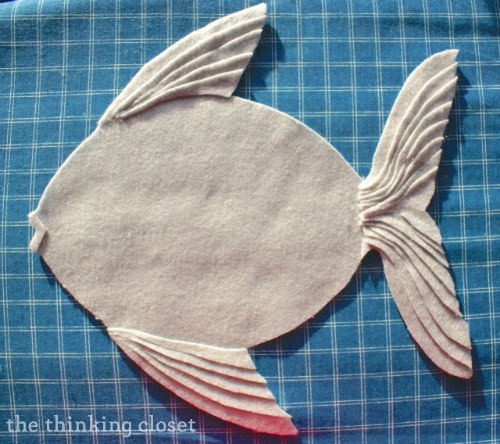 Layering felt strips to create a textured felt fish pillow! via thinkingcloset.com