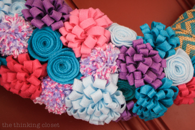 A bevy of beautiful felt flowers and pom poms really jazz up a spring to summer wreath!  via thinkingcloset.com
