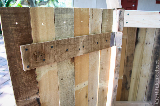 Creating the side door for the Rustic Pallet Recycle Bin.  Tutorial via thinkingcloset.com