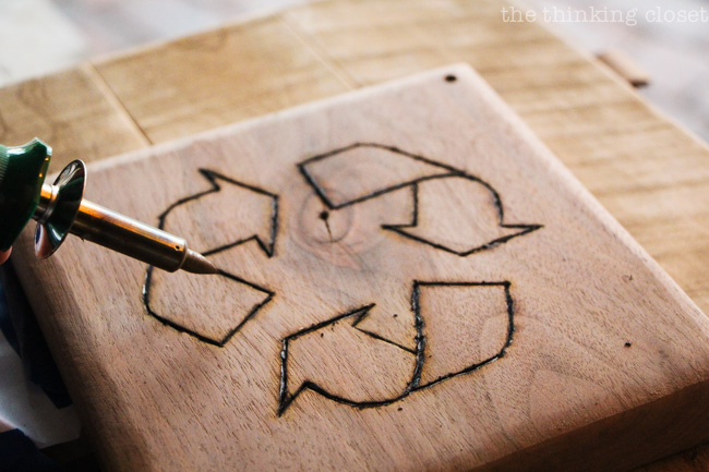 "Woodburning the recycle logo into the ""trap door"" of the Rustic Pallet Recycle Bin via thinkingcloset.com"
