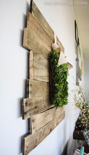 Rustic Vintage Spring Mantel: a pallet sign is the lovely backdrop for a boxwood wreath!  via thinkingcloset.com