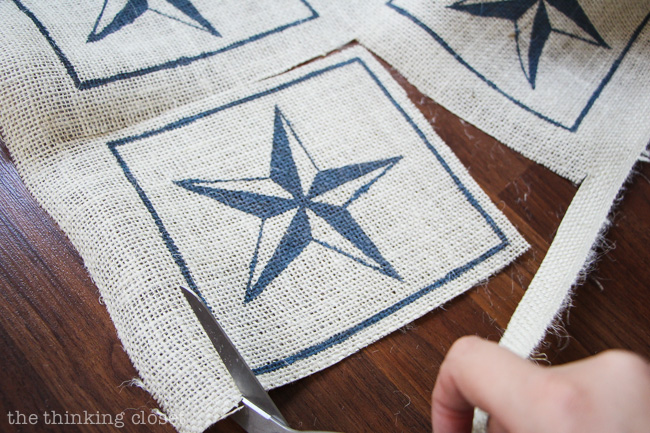 Cutting out the nautical star burlap squares.