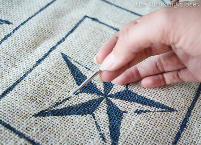 Adding final touch-ups to the nautical star burlap squares.