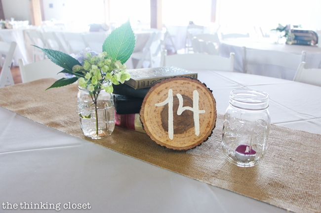 Creative centerpiece idea for a rustic vintage wedding: wood slice table numbers, a stack of vintage books, and mason jars filled with flowers and candlelight. Oh, and let's not forget the burlap table runners!