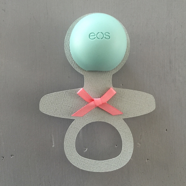 Charming Mint & Gray Baby Shower | Inspiration for planning a meaningful baby shower for a mom-to-be with creative ideas for decor, food, games, activities, a guest book, favors, and more! Here's a glimpse at one of the favors. Yep, that's an Eos lip balm in the center of the baby rattle. How clever is that?!