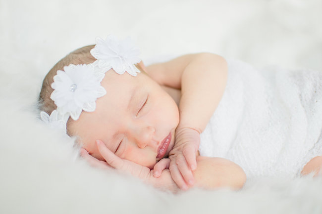 Juniper's 2 week newborn photography shoot: adorable hair bows, muslin swaddles, and a sweet smiling baby in a bucket. Brace yourself for the cuteness!