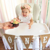 High chair decor for a Blooming First Birthday Bash, inspired by spring flowers in pink, blush, and white. DIY party ideas for a woodland floral-themed celebration, spring fling, or botanical garden party!