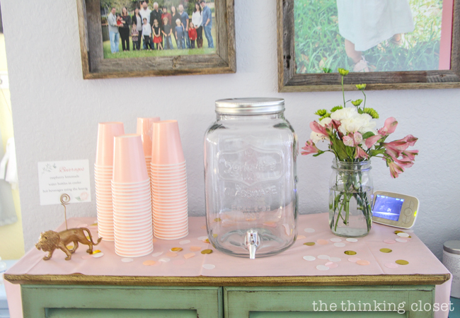 Raspberry lemonade, mini sign holders, and fresh flowers on display at a Blooming First Birthday Bash, inspired by spring flowers in pink, blush, and white. DIY party ideas for a woodland floral-themed celebration, spring fling, or botanical garden party!